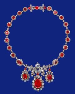 Ruby and diamond necklace - three large flat-cut rubios set in brilliant-cut diamond clusters were probably first made as a pair of earings and a pendant and were later adapted to form the centrepiece of the necklace - formerly in the Baring collection, the necklace was acquired by The Queen in 1964.
