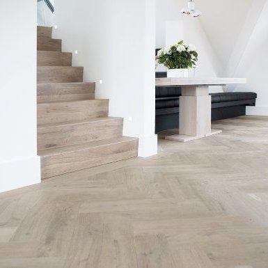 Grijs houten vloer - heel mooi zo in combinatie met de witte muren en de houten trap.