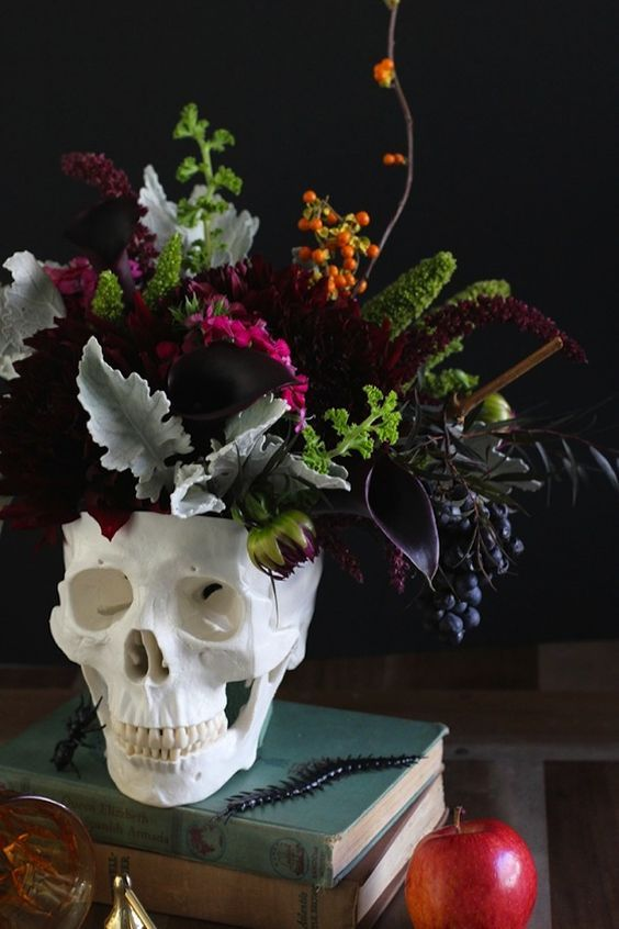 36 ideas to throw a halloween wedding with style 11 moody flowers and leaves in a skull vase lovely wedding ideas pinterest the skulls
