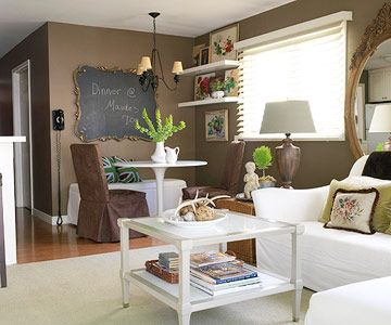 The kitchen's deep wall color continues into the casual family room as does the use of airy white furnishings and accents