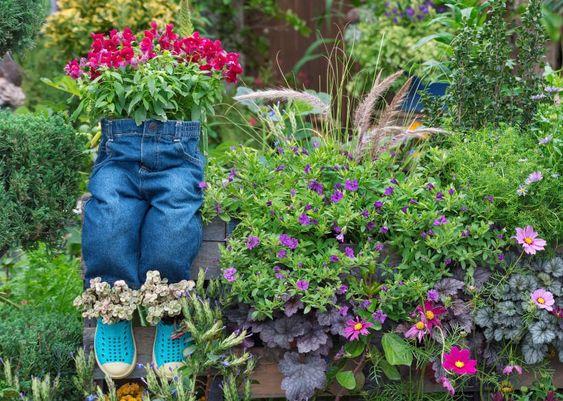 Ein paar Hosen suchen, als ob sitzend auf einem Holzzaun als Pflanzer Blumen verwendet wird. Ein paar Crocs, auch verwendet als Blume Pflanzer, direkt unter der Hose verbunden sind, mit den Blumen sprießen beide erstellen eine spielerische Stimmung zu diesem Blumengarten.