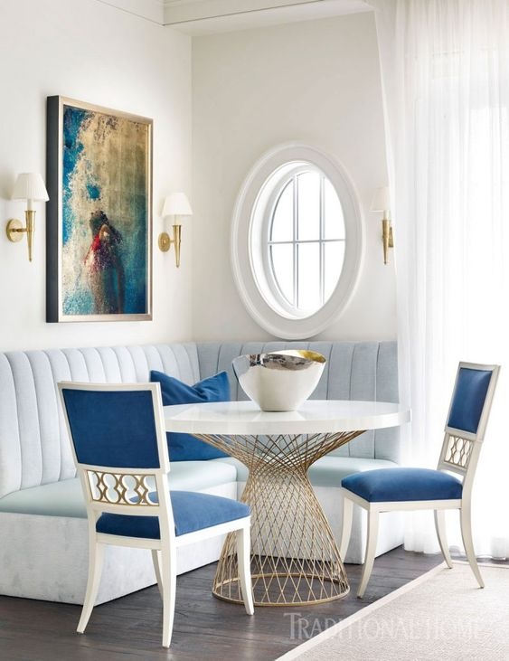 Beautiful blue banquette in kitchen with #ovalwindow and #classicdecor. #blueandwhite #rounddiningtable