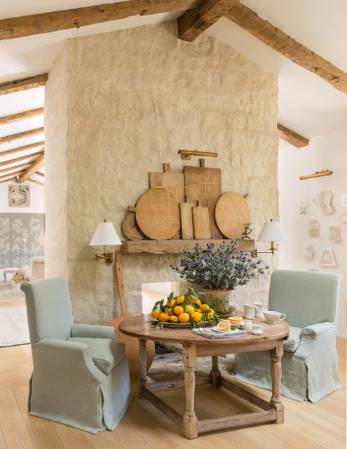 Breakfast room decor with French farmhouse, modern farmhouse and French Country interior design styles. Slipcovered arm chairs, a round antique dining table, and a magnificent limestone fireplace decorated with rustic bread boards. #breakfastroom #diningroomdecor #patinafarm #frenchcountry #limestone #fireplace #interiordesign #frenchfarmhouse #designideas