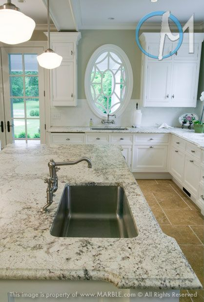 Here the cabinets are actually relatively basic, but the slab, especially on the island, helps liven things up. You get a really elegant feel from the cut of the piece both the edge and the overall shape.