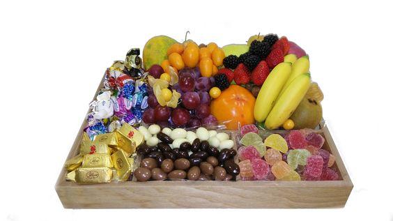 Bandeja de madera compuesta por un surtido de bombones, fruta italiana, frutos secos bañados en chocolate todo acompañado por rica fruta fresca: mango, papaya, persimón, manzana, uvas, kiwis, bananitos, tamarindo, physallis, fresas, moras y kumquat.