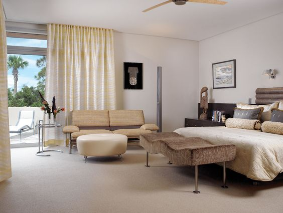 Brueton's bench adds curves next to an Il Loft sofa, an ottoman in Nina Campbell fabric from Ammon Hickson, and an Eileen Gray occasional table in this master suite.