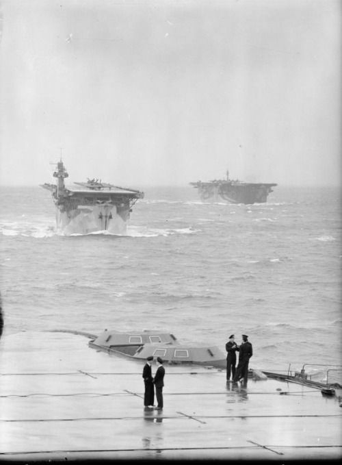 WW2. After end of the flight deck of HMS VICTORIOUS in the foreground with the carriers HMS BITER and AVENGER following.