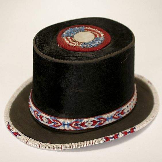 <b>Beaded beaver skin top hat.</b> Native American geometric design band and trim. American flag motif top with mother of pearl button.