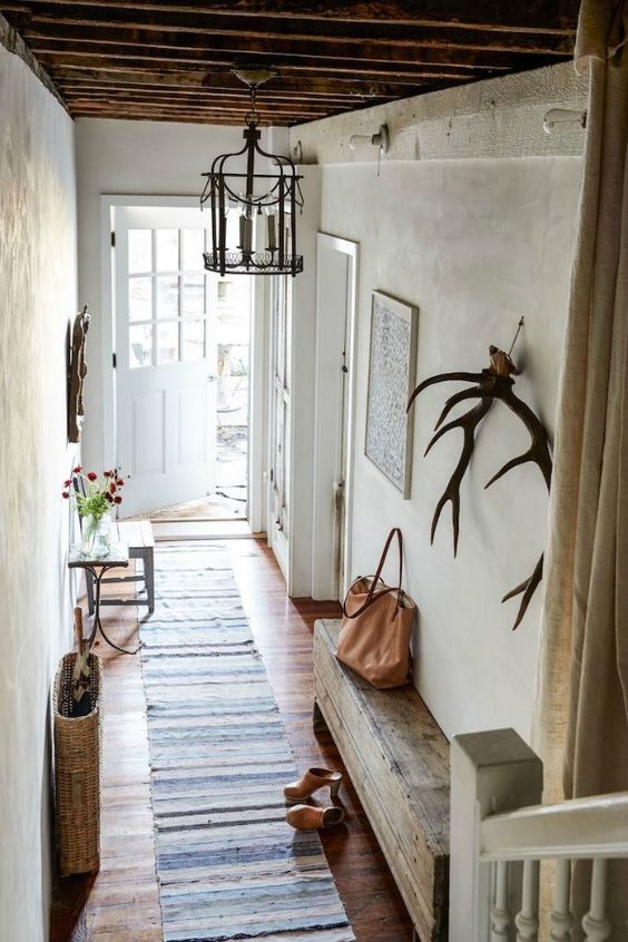 French farmhouse decor and Rustic French Country decor inspiration from a gorgeous European farmhouse style New York apartment styled by Zio + Sons. Plaster walls, antlers, and timeless design ideas. #Frenchfarmhouse #Frenchcountry #rusticdecor #interiordesignideas #vintagestyle #hallway #entryway #antlers #decoratingideas