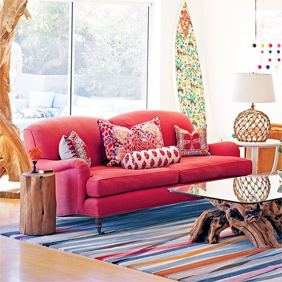 21 Homes That Prove Surf Is Chic // surfboards as decor // red George Sherlock sofa, striped rug, burlwood and glass coffee table, Japanese buoy lamp, stump stool, Eames Hang-It-All rack