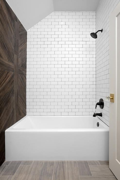 A Drop In Bathtub Is Accented With White Subway Tiles Finished With Black Grout Lined With A Mat White Subway Tile Bathroom White Subway Tiles Wood Tile Shower