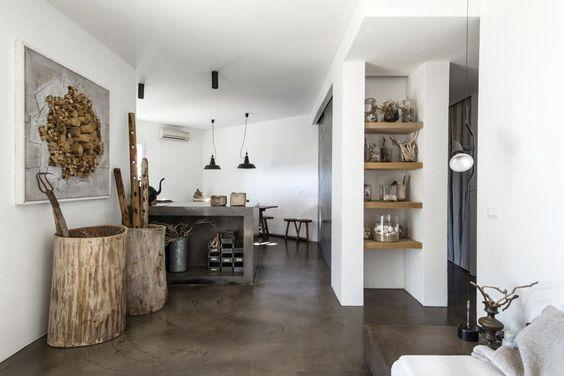 Masseria nella campagna pugliese. Il bancone allungato della cucina divide il soggiorno dall'angolo cottura. Nelle vecchie tinozze di legno riposano gli attrezzi agricoli.