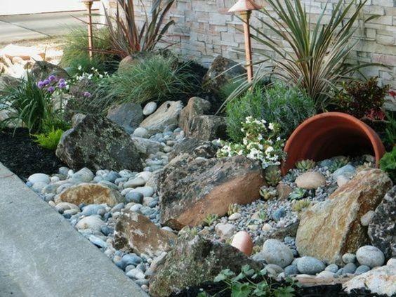 un coin nature longeant le mur d une maison, des galets et plus grosses pierres, éclairage, grand pot à fleurs, arbustes bas, rocaille fleurie