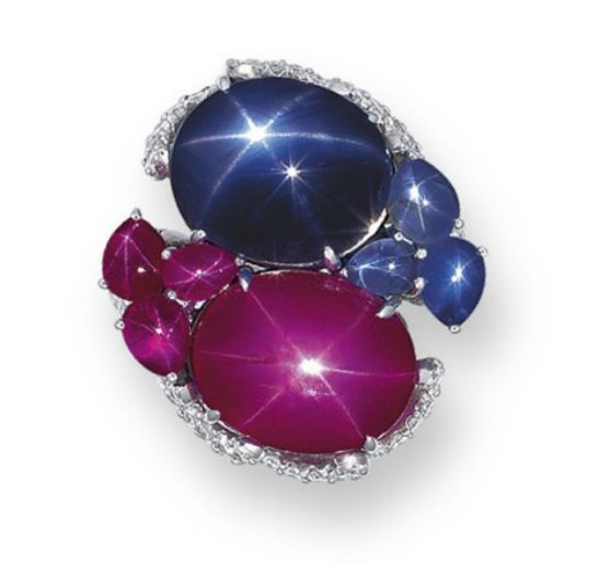 A STAR SAPPHIRE, STAR RUBY AND DIAMOND RING  Set side-by-side with a cabochon star sapphire weighing approximately 13.36 carats and a cabochon star ruby weighing approximately 13.63 carats, further flanked by cabochon star sapphires and star rubies, to the brilliant-cut diamond scrolling half-hoop, mounted in platinum