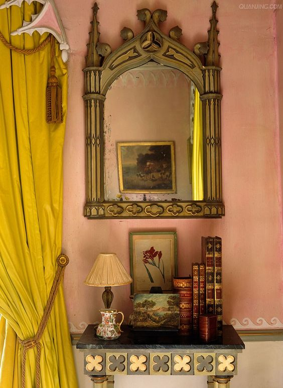 Gothic decor and a peachy European pink plastered wall with a bright mustard yellow drape.