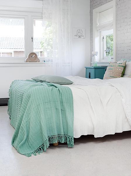 ベッドルームはホワイトの割合高めですが、その中でターコイズのリネンカバーとサイドテーブルがアクセント。自然素材はクッションと壁面のタイルで取り入れています。