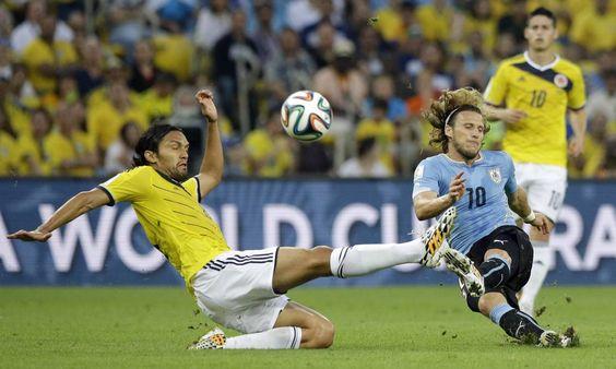 O uruguaio Forlán divide a bola com o colombiano Aguilar
