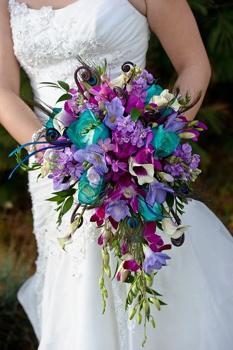 Purple, teal, and white cascade bridal bouquet with peacock feathers.