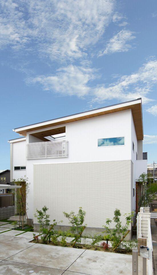 片流れの屋根が印象的な外観 白いタイルと軒の木目がナチュラルな
