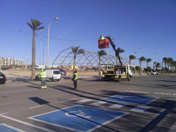 Los operarios del Ayuntamiento de Vinaros, intentan por segunda vez instalar la iluminacion para las casetas, despues de que el primer dia el viento se lo impidiera
