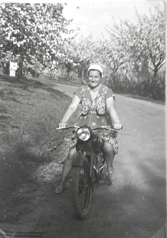 A grandmother hanging on her motorcycle in 1951.