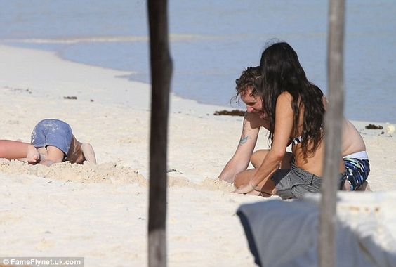 Beach time: The giggling couple took time to play in the sand with a young child