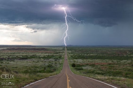 """Top 10 Weather Photographs: 6/16/15 """"Lightning Captured at Just the Right Time"""" – This thunderstorm were pretty electrical and has produced many lightning strikes in front of us, One of them has had the good idea to come hit a power pole located in the exact continuation of the road, while the white car that we can see a bit further just came toward us."""