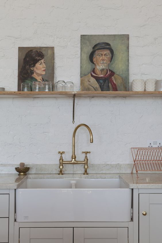 Painted brick wall and pale kitchen with open shelving