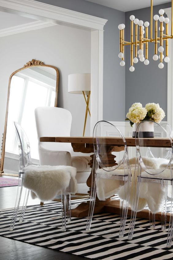 The dining table is surrounded by fur-covered Lucite chairs. | Dining Room Ideas. Dining Room Table. Dining Room Design. Home Decor. Find more dining tables at: brabbu.com/en/all-products.php#dining-tables