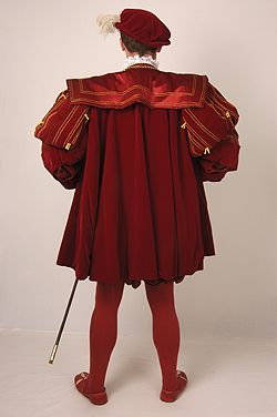 NINYA MIKHAILA - HISTORICAL COSTUMIER 1540s courtier's suit made for JMD&Co at Hampton Court Palace. Based on a painting in the Royal Collection of an unknown man. Suit consists of doublet, hose and gown and bonnet in red silk velvet with red and gold striped 'pullings out'. Blackwork embroidery on shirt worked by Jane Huggett.