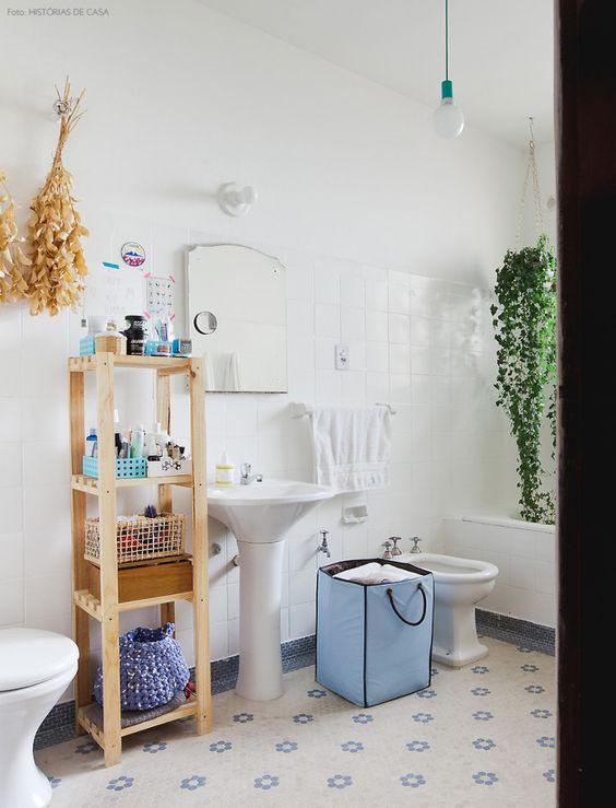 Banheiro com revestimentos originais do prédio como o azulejo branco e piso de colmeia.