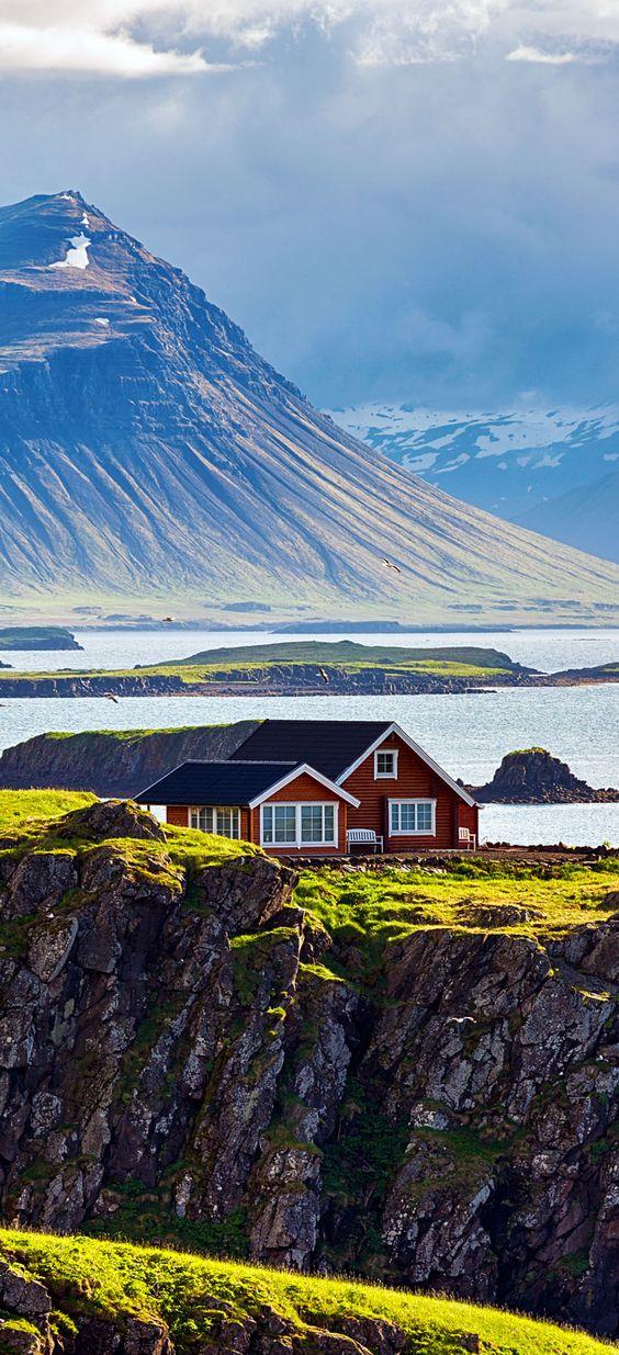 Cabaña roja hermosa en Islandia paisaje costero.