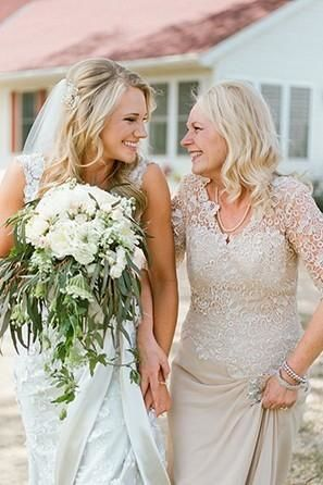 The mother of the bride smiles at her daughter right before the wedding ceremony begins.: