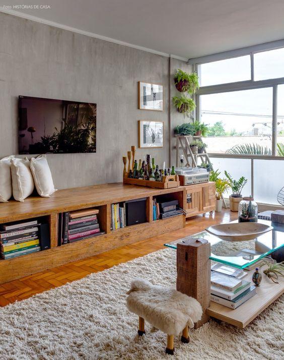 Sala de estar com parede de cimento queimado e banco de madeira de demolição.:
