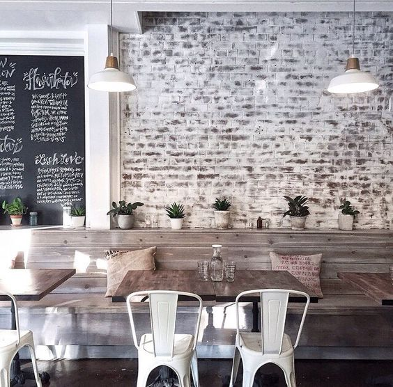 Love this casual scheme- especially the partially exposed brickwork and white metal chairs .