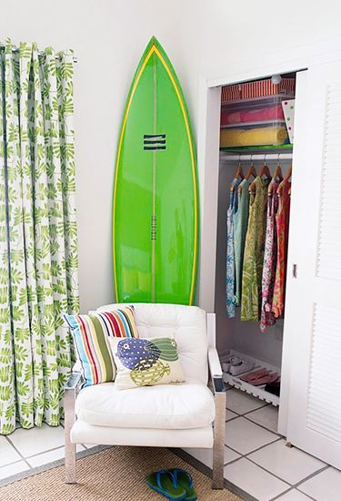 21 Homes That Prove Surf Is Chic // surfboards as decor // green surfboard, green botanical curtains, white canvas and chrome armchair, Lilly Pulitzer dresses, closet