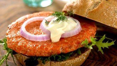 """""""Hamburguesa"""" no tiene por qué ser sinónimo de """"comida chatarra"""", el salmón es una excelente opción para crear una tentación muy saludable. Acompaña con una mayonesa de hierbas -o un aderezo a base de yogur natural- y tus vegetales favoritos."""