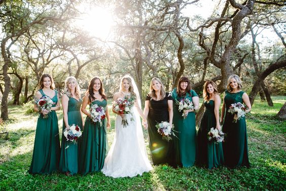 Texas winter wedding with green mismatched bridesmaid dress and maid of honor in black dress to match black suits and ties of groomsmen.