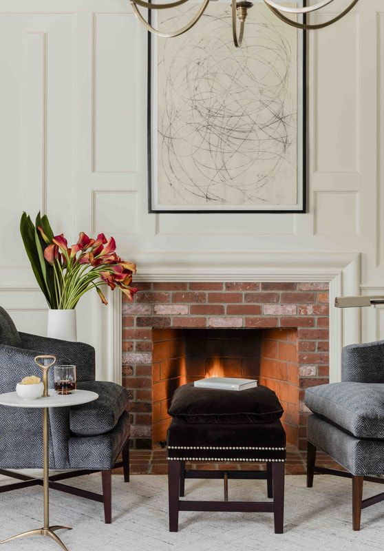 Cozy Fireplace Sitting Area With Arm Chairs Foot Stool Art And Chandelier Lisa Tharp Contemporary Home Furniture Boston Interior Design Traditional Decor