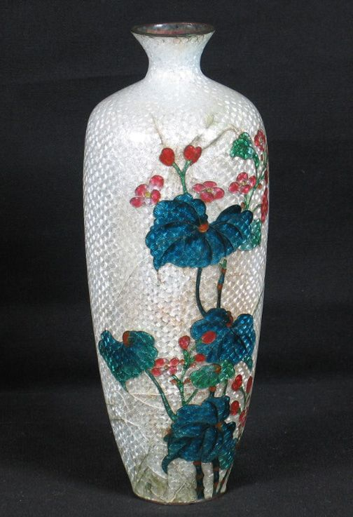 "JAPANESE FOIL ENAMEL VASE Japanese foil cloisonne enamel vase, white foil ground, red green and blue floral decorated front. No mark. Size: 7 1/4""H, 1 1/4""Diam. top, 3""Diam. widest part, 1 1/2""Diam. base. Condition: bottom cut off, major cracking in back, some staining in front."