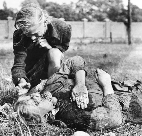 A ten-year-old Polish girl named Kazimiera Mika mourns over her sister's body. She was killed by German machine-gun fire while picking potatoes in a field outside Warsaw, Poland, in September of 1939. (AP Photo/Julien Bryan)