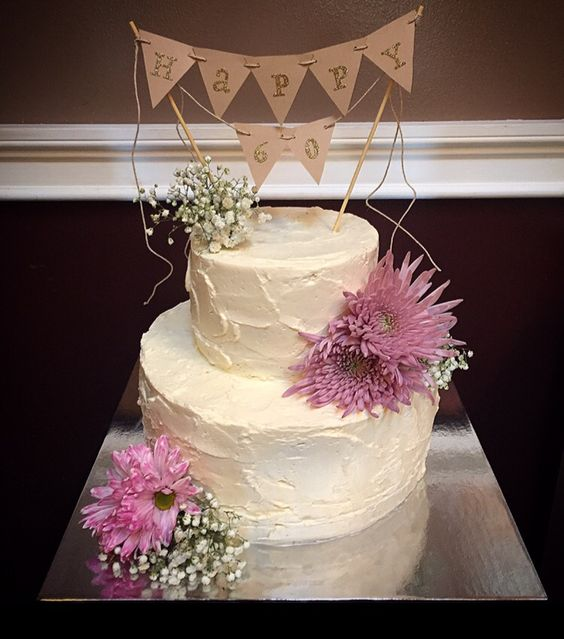 60th birthday cake. Rustic looking Italian buttercream. Adorned with fresh flowers and topped with a custom made cake banner!