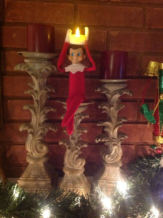 Elf posing as a candle.... Wonder if anyone will notice! He lights up our life!!! Lol