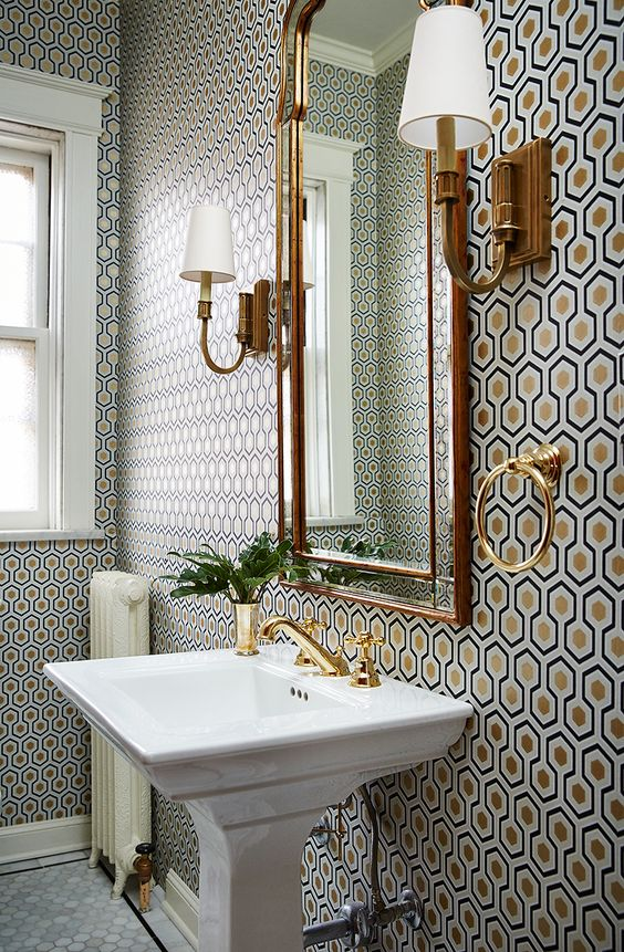 small bathroom with a lot of pattern on wall, wallpaper, gold mirror, wall sconces