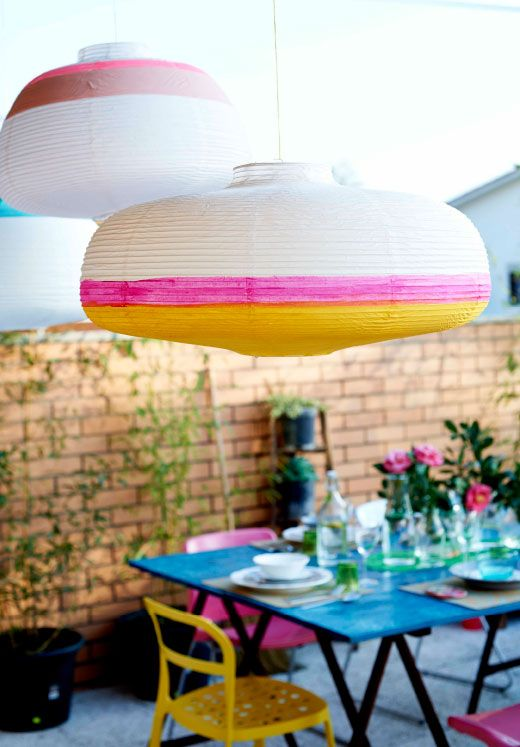 """Painted VÄTE lamp bunting with dining room table. - """"'Instead of using them for lighting, we painted these paper lamp shades to create decorations. Each one takes just a few minutes to do but they create instant impact and help define the space from the rest of the home. It's lovely to watch them sway gently in the breeze.'"""""""