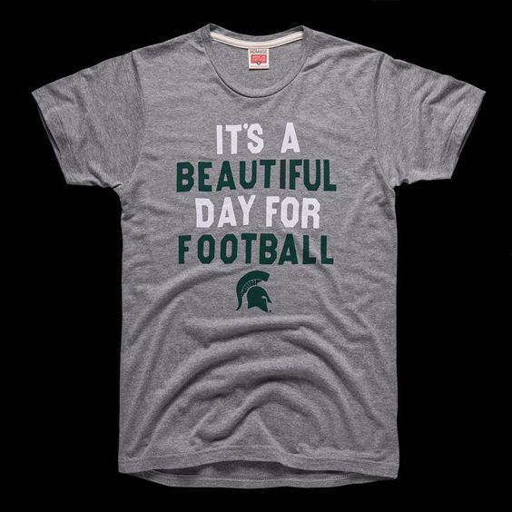 """Nothing speaks to Michigan State's rich football tradition and the school's six national titles more than the six-word phrase that kicks off every game at Spartan Stadium. And regardless of the weather—T-storms, hail, frigid temperatures, a combination of all three—right before kickoff, Spartan Stadium joins the game's announcer in declaring, """"It's a beautiful day for football."""" MADE IN USA"""