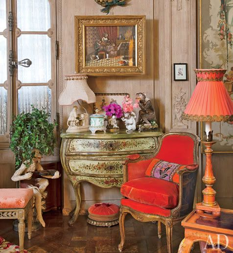 Curious Places: Iris Apfel's apartment (NY City/ New York)-Love her style, red chair, coral lampshade, French console, with picture