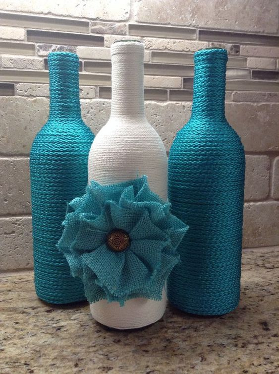 This listing is for a set of three wine bottles which have been hand wrapped in turquoise and cream yarn. Center bottle is embellished with