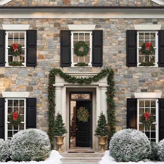 Beautiful classic stone house exterior with greenery, wreaths, and black shutters