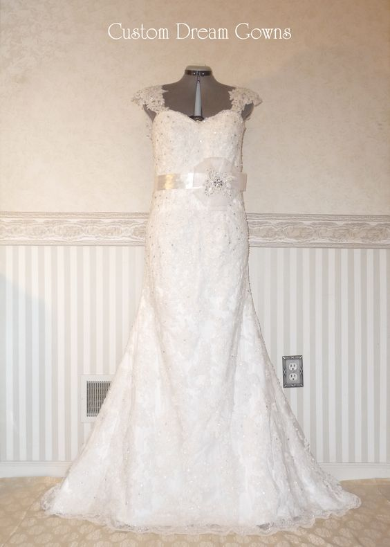 Romantic Allover Lace A-Line Gown with Sweetheart Neckline, Elegant Detachable Cap Sleeves, Beautiful Floral Belt, A-Line Lace Skirt, Court Train, Back Corset Close. #customdreamgowns #weddingdress #weddinggown #customdress #laceweddingdress #aline #sweetheart #courttrain #crystals #wedding